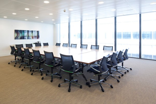 tidy meeting room with office chairs neatly and perfectly arranged around table and abstract picture mounted on the wall