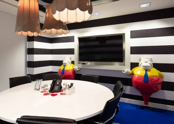 "alt=""tweedle dum and tweedle dee holding screen in a meeting room with black and white striped wall, round table and chairs and phone"""