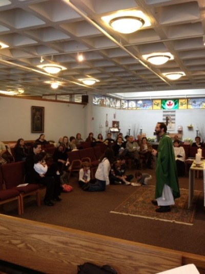 Fr. Manny Borg invites the children of St Nicholas to come forward for the sermon.