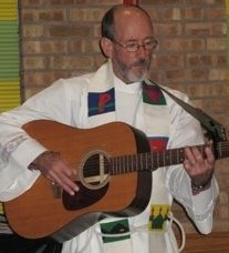Father Paul T. Brouillette, vested to preach or preside at the altar, playing the guitar