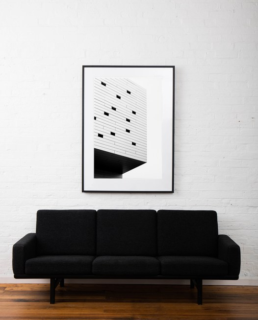 Large vertical Black and White Abstract photo of a bluiding in Urban Europe farmed in black timber on wall above sofa