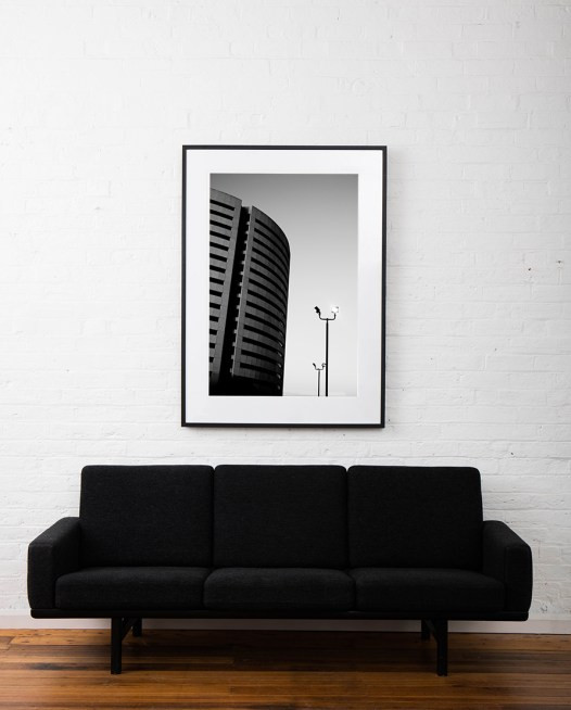 A large Vertical black and white photographic art print of a building and street lamps framed in black timber on wall above sofa