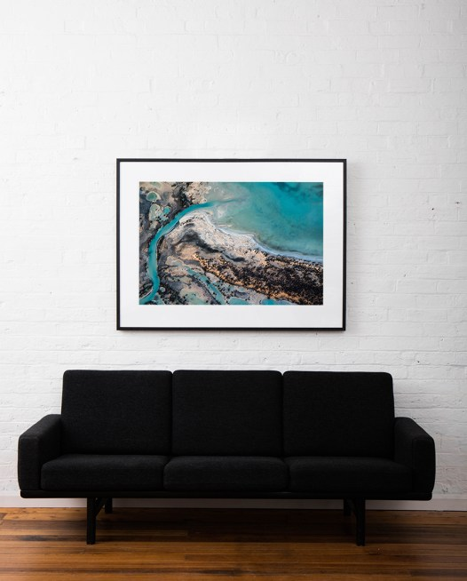 A horizontal abstract aerial photo of water taken in Australia in colour of blue, green and grey framed in black timber on white wall above sofa
