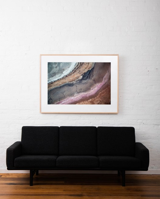 A horizontal abstract, aerial photo of Australia water in pink, purple, and red framed in raw timber above sofa
