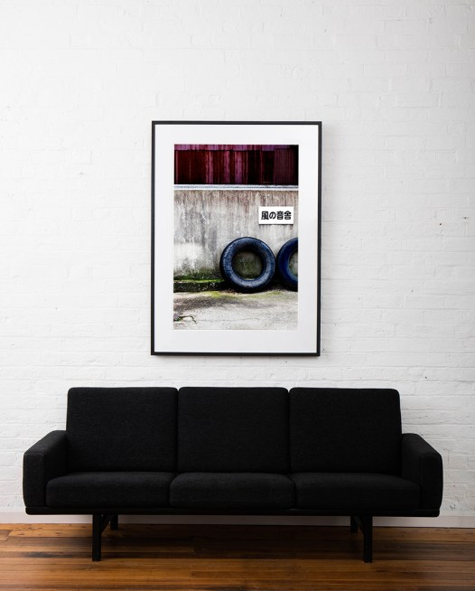 A large vertical abstract photo of 2 wheels taken in Urban Japan. Framed in black timber on white wall above sofa