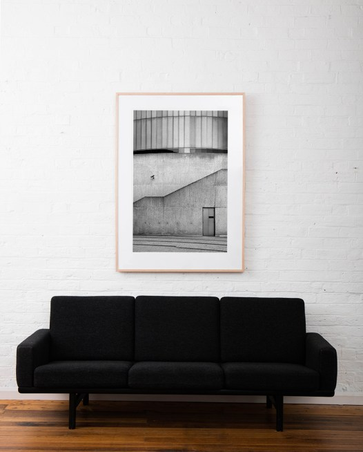 Large Vertical Black and white photographic art print of buildings and doorway by Allan Moyle framed in raw timber above sofa