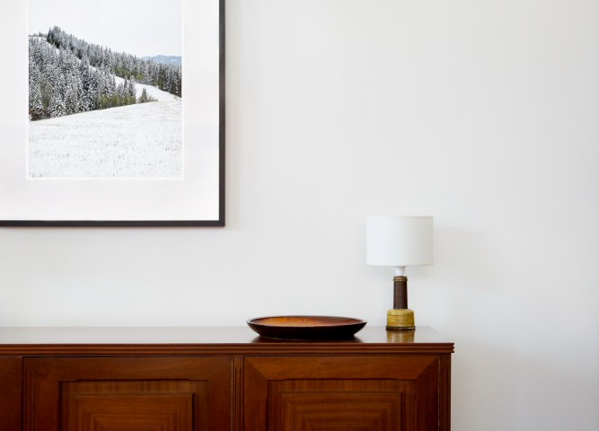 A vertical photographic landscape print of snow, moutain and trees taken in North America in shades of white black and green framed in black timber on wal above cabinet