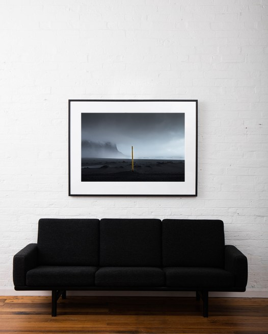 Large Icelandic landscape of sea, mountains, waves and clouds with a yellow pole in the middle of beach framed in black timber on wall above sofa