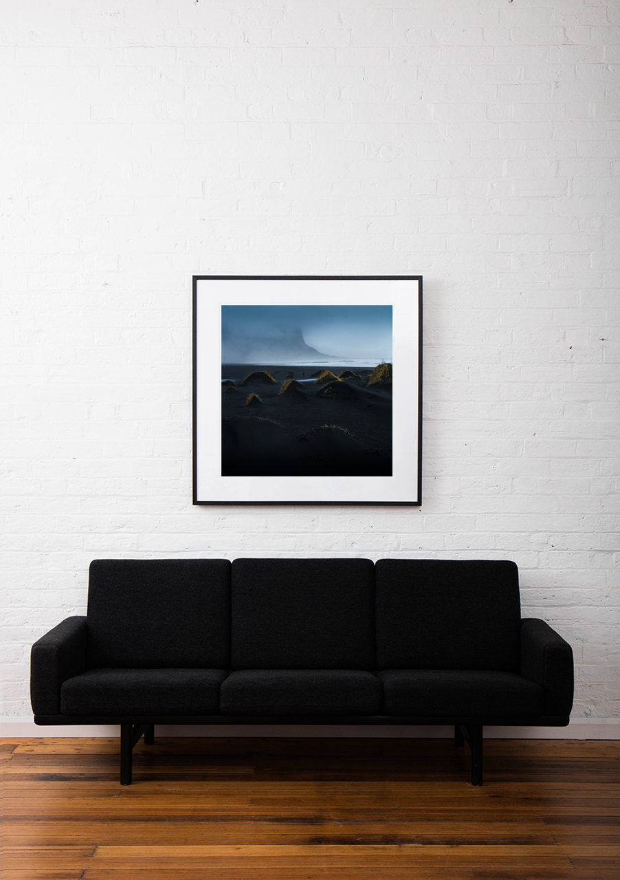 A misty photographic image of icelandic landscape of beaches, sea and mountains in shades of blue framed in black timber on wall above sofa