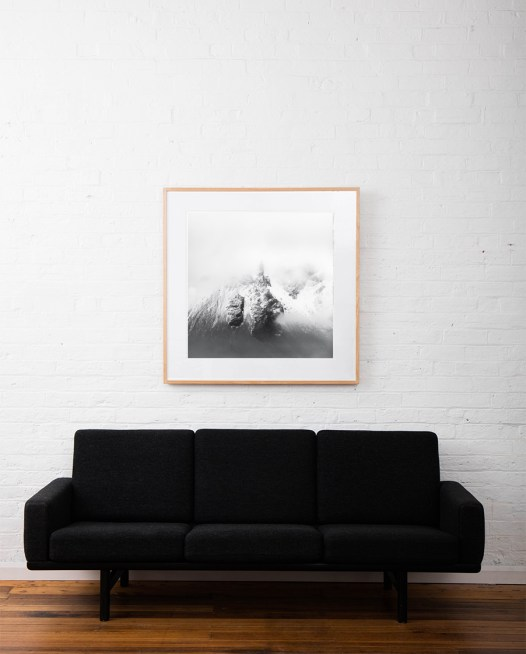 A photographic prints of icelandic mountains covered snow framed in raw timber on wall above sofa