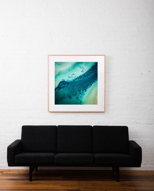 A Square Abstract, Aerial photo of Australia landscape in green and blue framed in raw timber on white wall above sofa
