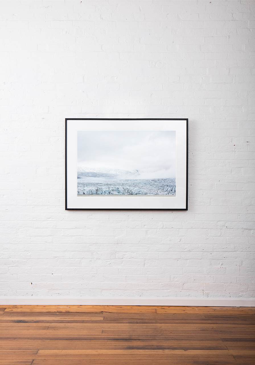 Large Iceland Lanscape of Falling Glacier in blue and whilte. Framed in black timber on white wall