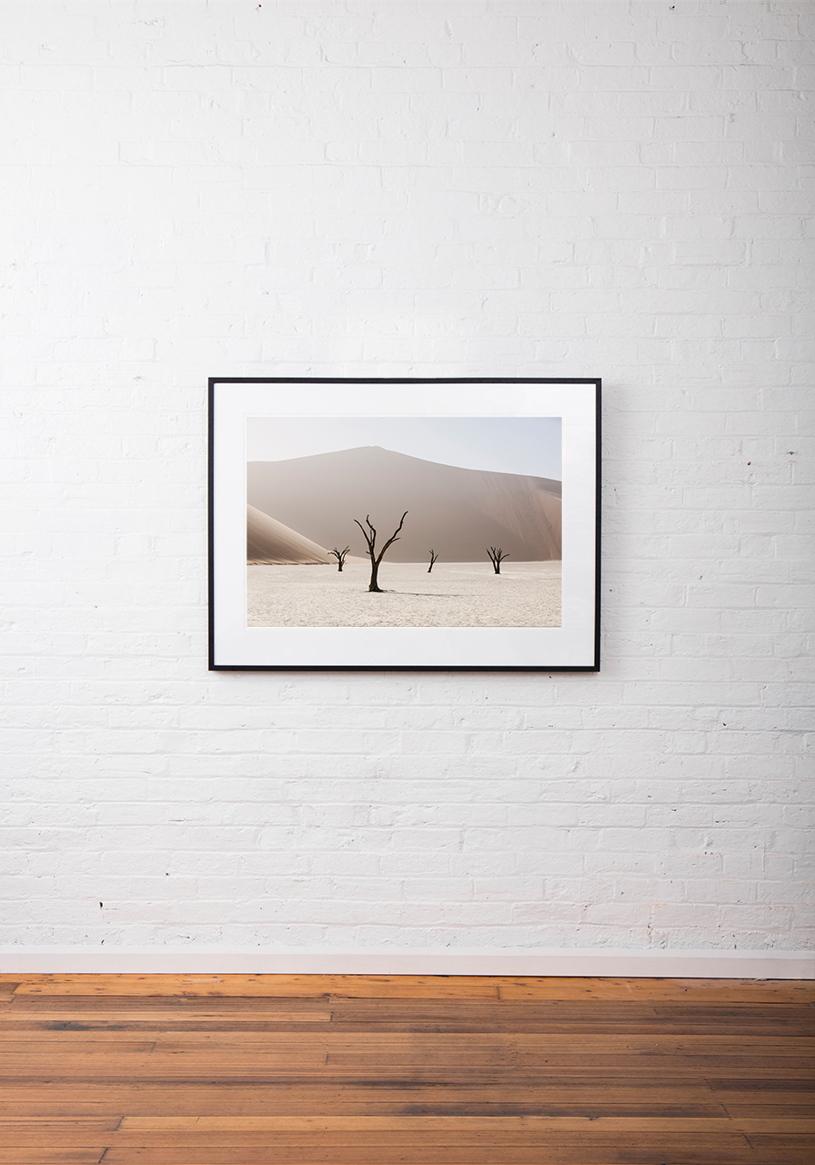An Abstract photo of African Landscape of mountains, sand and trees in brown, pink and white framed in black timber on white wall