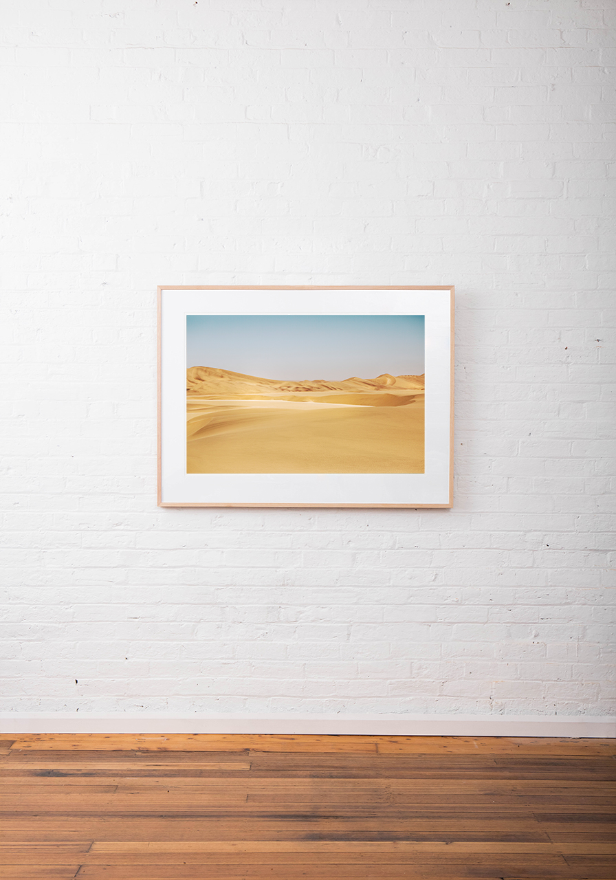 A photograph of Africa desert in yellow sand and blue sky framed with raw timber on white wall