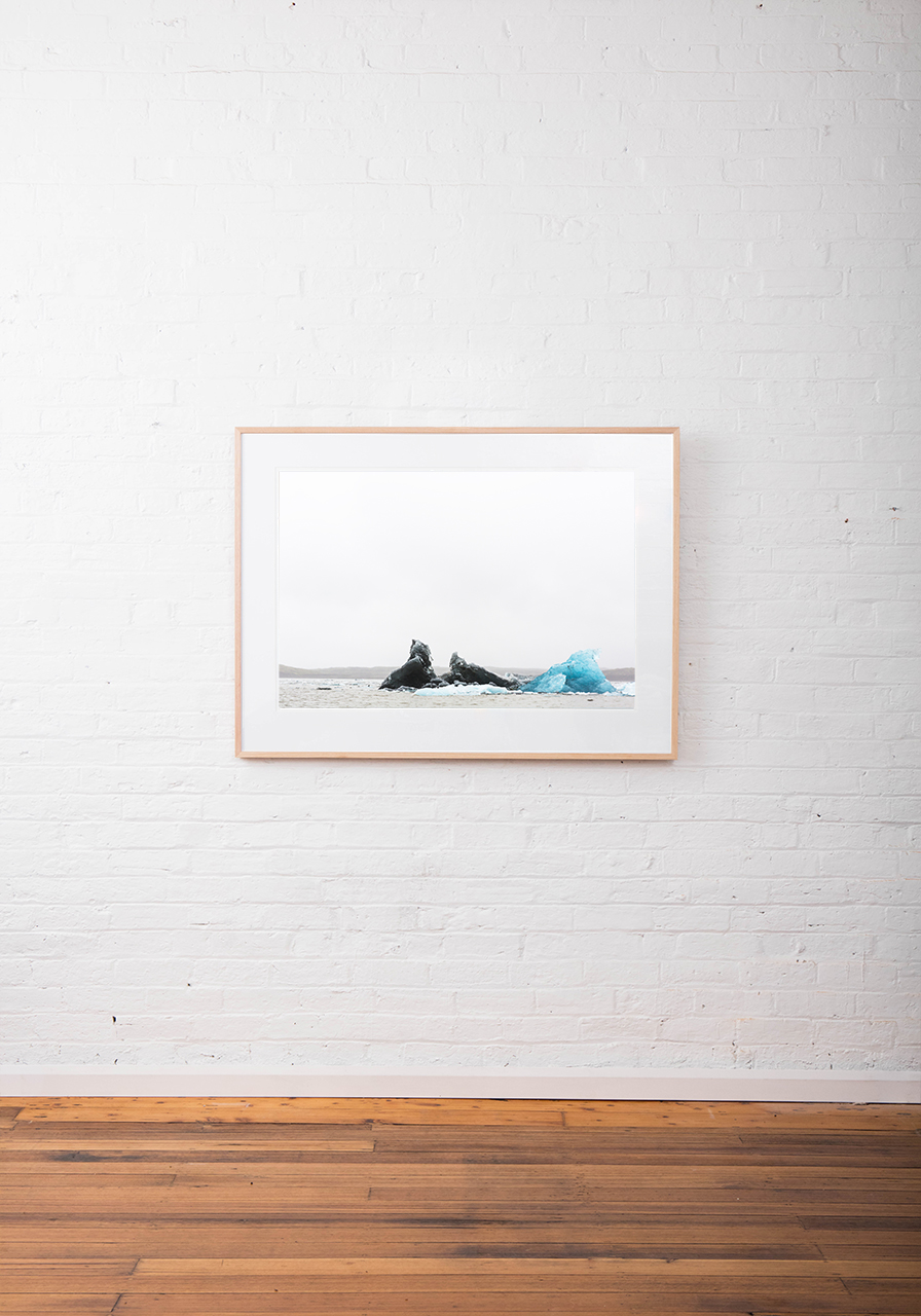 Large photographic art image of glacier, iceberg floating in water taken in Iceland Landscape. Framed in raw timber on white wall
