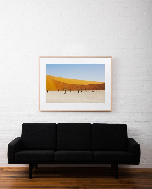 A abstract photo of Africa Landscape in yellow, gol and blue framed in raw timber on white wall above sofa