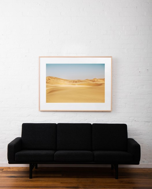 A photograph of Africa desert in yellow sand and blue sky framed with raw timber on white wall above sofa