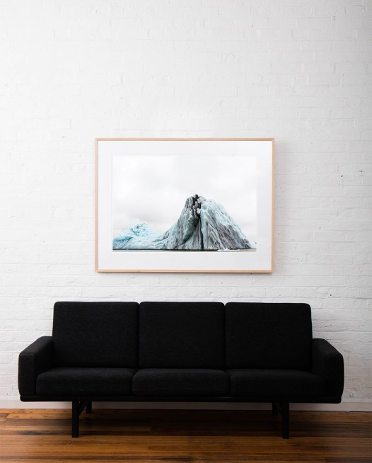 Large Blue and white Icelandic landscape of water, sky, glacier and snow. Framed in raw timber on white wall above sofa