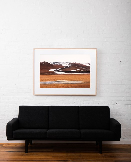 A abstract Iclandic Landscape photo of Mountains and snow in white ,brown and orange framed in raw timber on white wall above sofa