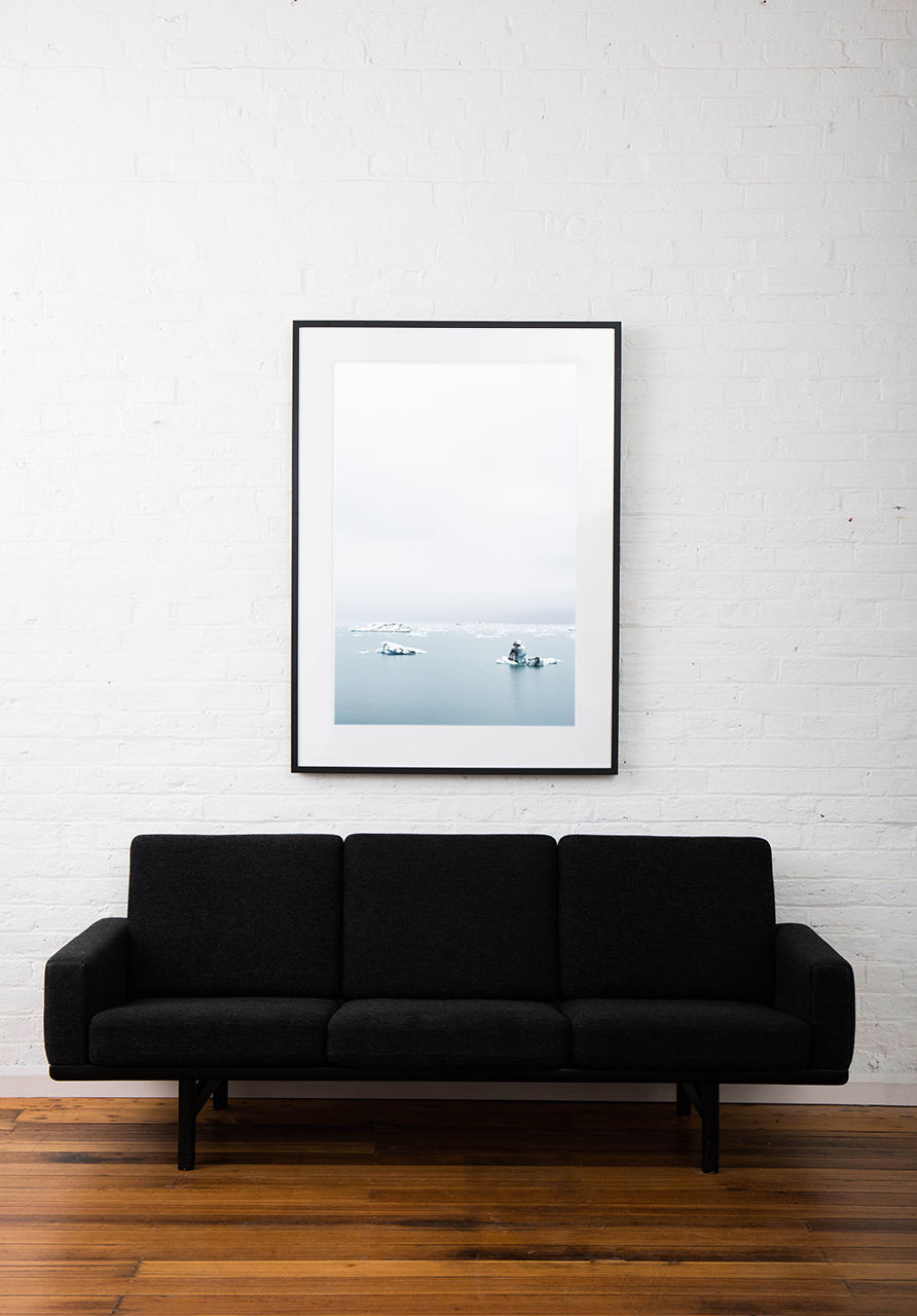 Large Print of Icelandic Landscape of glacier, snow water and sky in blue and white. Framed in black timber on white wall above sofa
