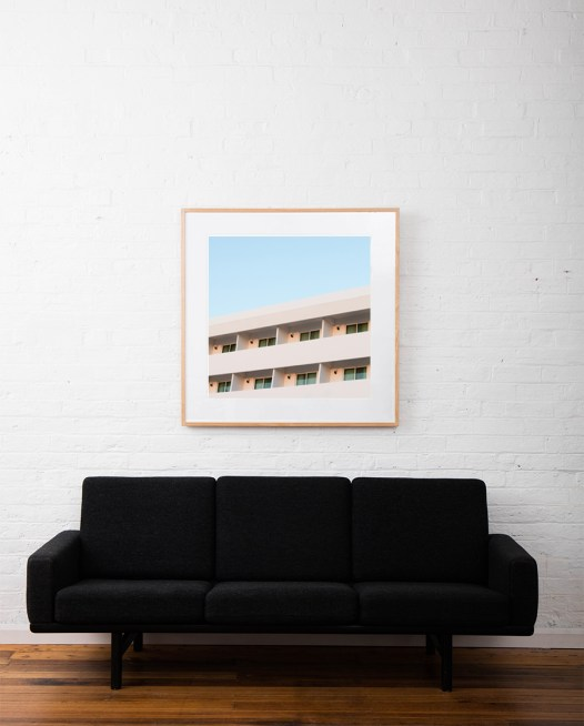 Architectural building taken by Eizabeth Bull in Central American Urban Landscape captured in Pink and Blue tone in a Modernism Art Print framed inraw timber square frame on white wall above sofa
