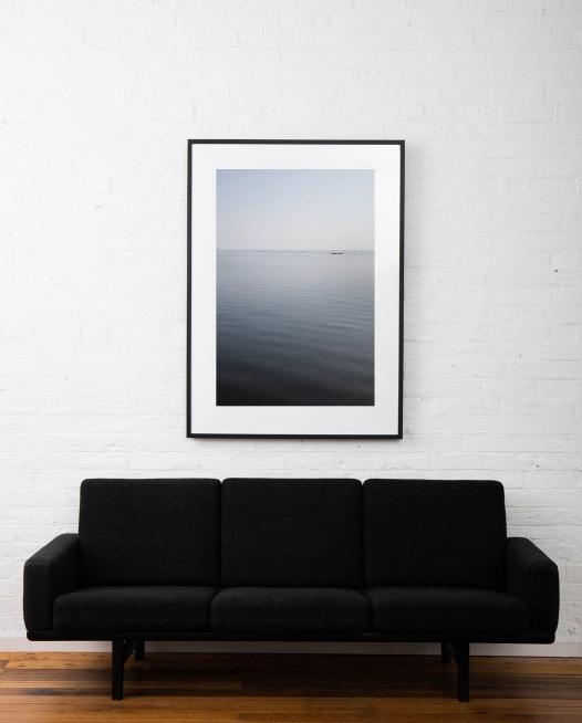 A large vertical abstract image of water - blue grey, taken in India Landscape by Elizabeth Bull framed on black timber frame on white wall above sofa