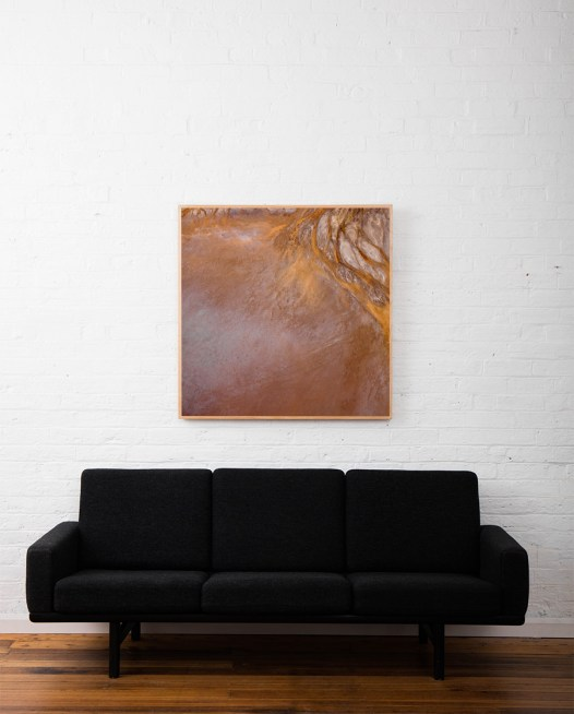 An Aerial photographic print of Lake Eyre in brown and orange colour framed in raw timber above sofa