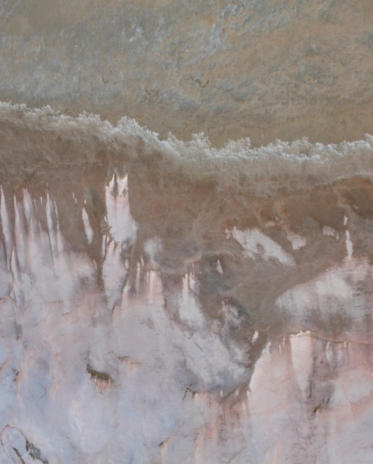 An aerial photo of inland Australia landscape in grey pink and brown color.