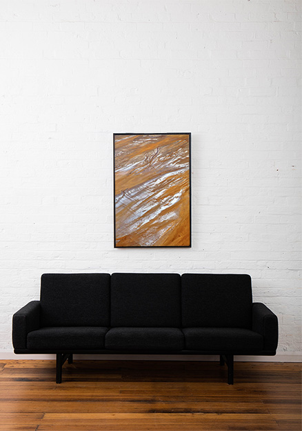 An aerial landscape photo of Australia in brown yellow and silvery colour framed in black timber frame above sofa