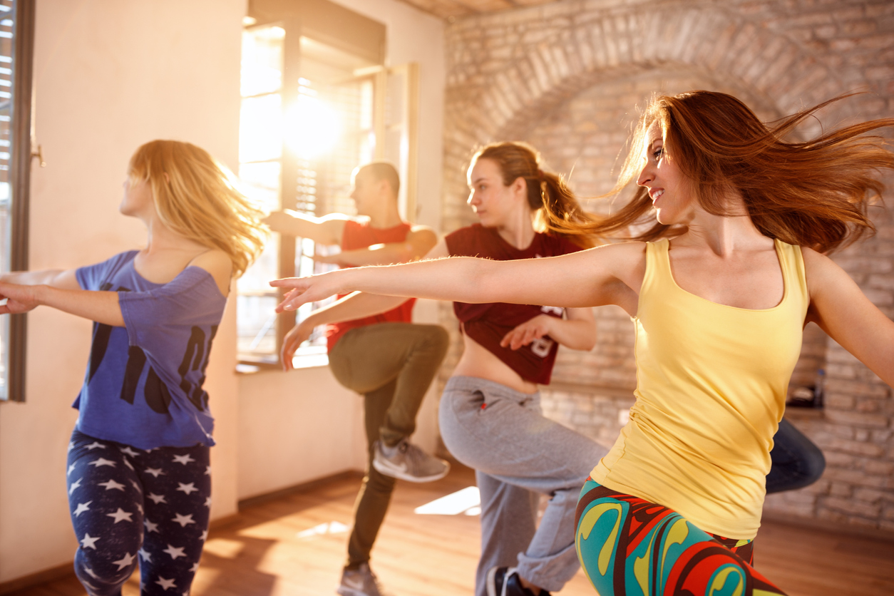 three women and one man dance to the music in a dance fitness studio class