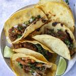 crispy carnitas tacos on plate with extra tortillas