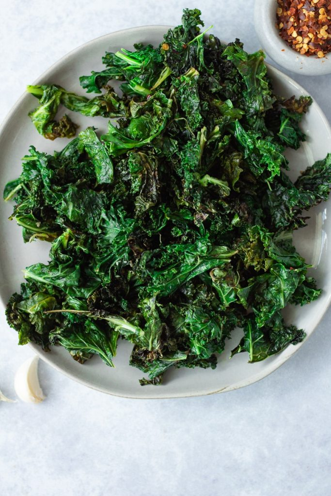plate of sautéed kale with small bowl of pepper flakes