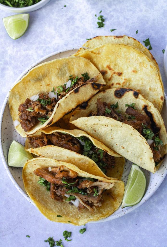 crispy carnitas tacos with toppings on plate