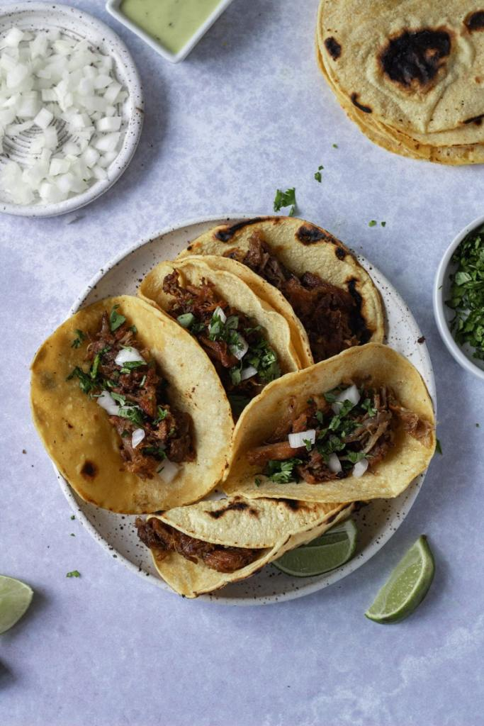 Crispy carnitas tacos with toppings around plate