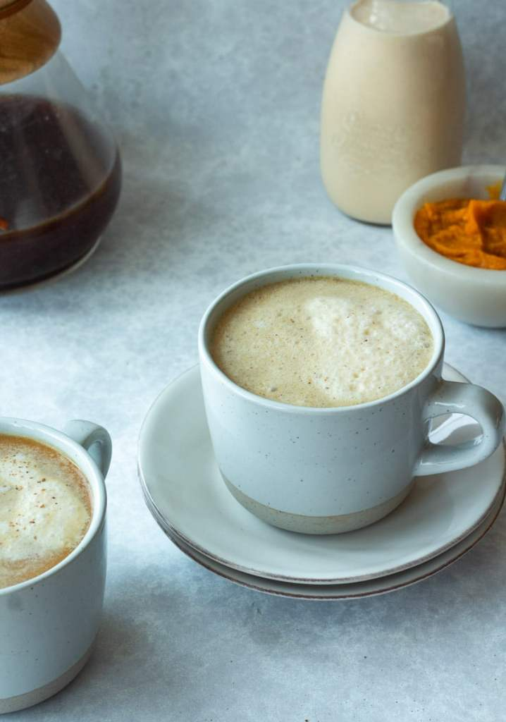 2 mugs of pumpkin cream cafe au lait with pumpkin and coffee in back