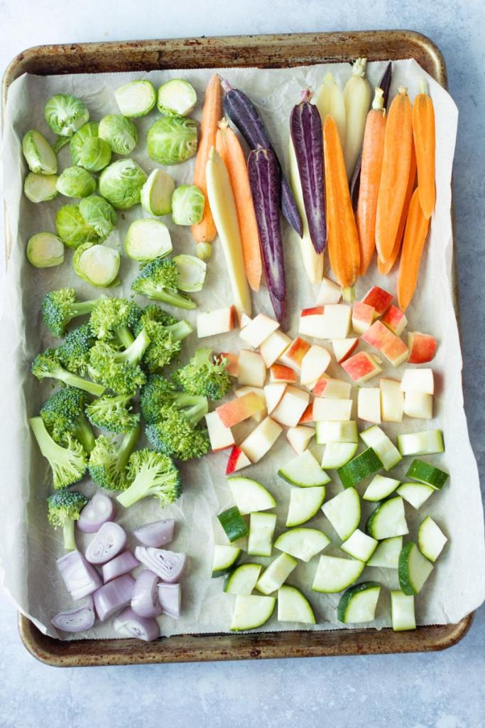 raw, cut up vegetables on sheet pan