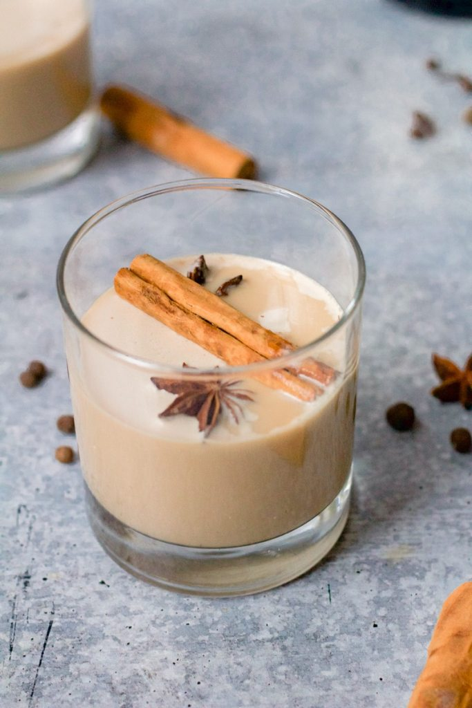 glass of white russian with cinnamon stick and star anise floating on top