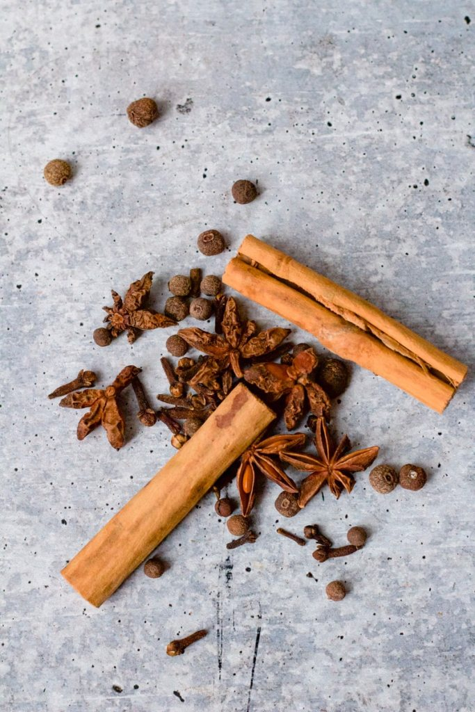 pile of cinnamon sticks, allspice berries and cloves on background