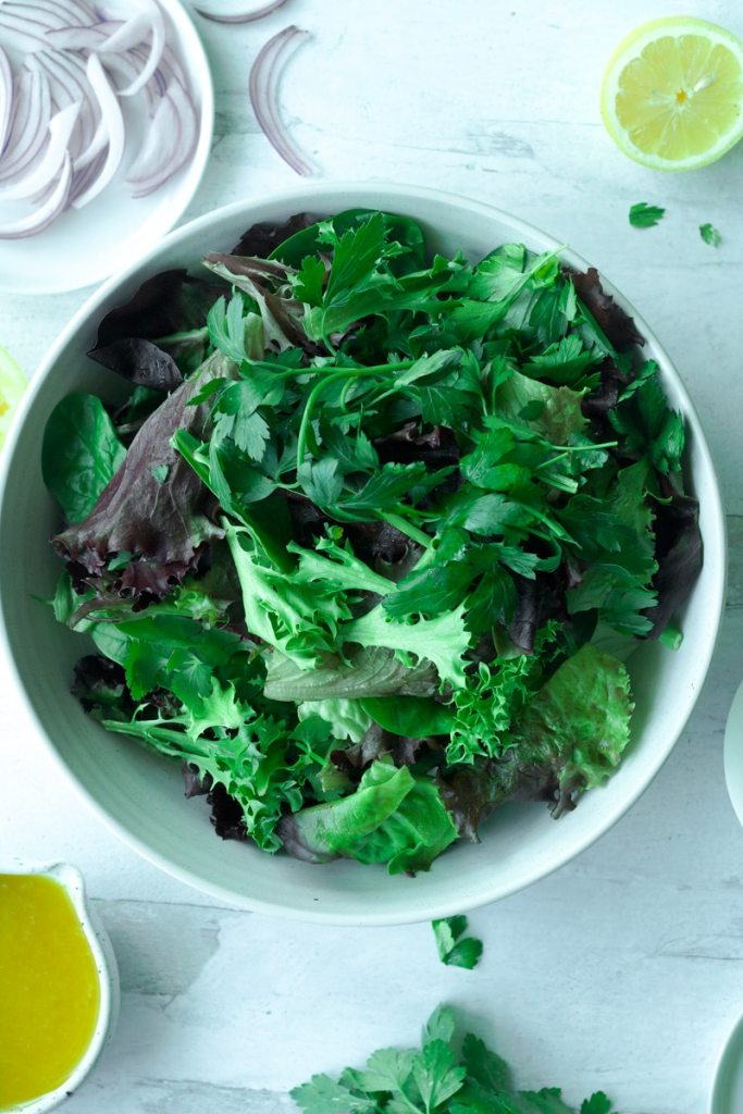 big bowl with greens surrounded by small plates with sliced red onion, herbs and a small bowl of salad dressing