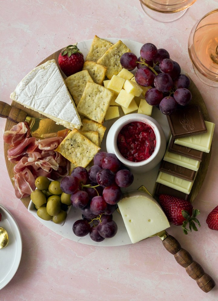 board with cheese, chocolate, olives, strawberry jam and crackers