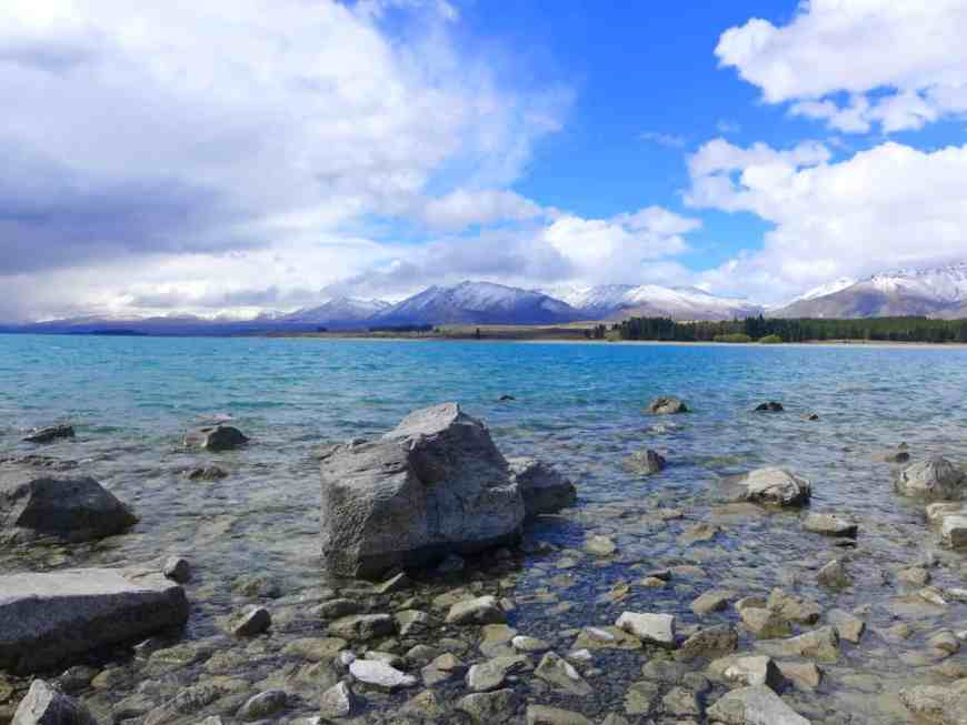 New Zealand's Lake Tekapo, a gorgeous lake with glacier minerals backed by snow-capped mountains. Visit this area to see the famous lake and chapel, hike the Hooker Valley Track, and gaze at the bright stars...what to do on your visit!