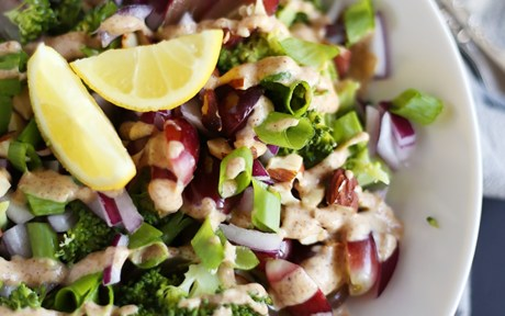 Vegan Gluten-Free Easy Broccoli Salad with almond lemon dressing topped with lemon wedges