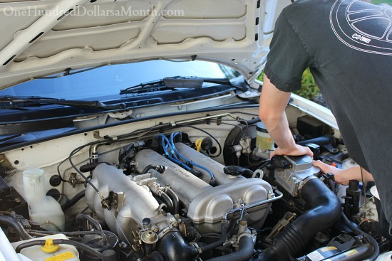 boy looking into car engine