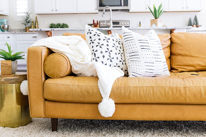 tan leather couch living room looks why the sven sofa is perfect for in your one article charme with white pom blanket and black throw pillows