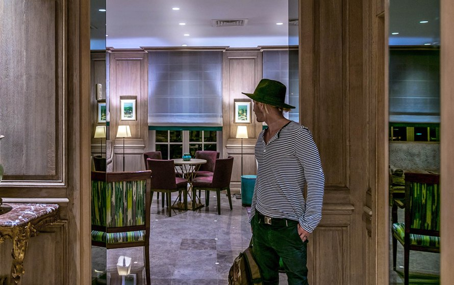 man in hat in hotel lobby looking the other way