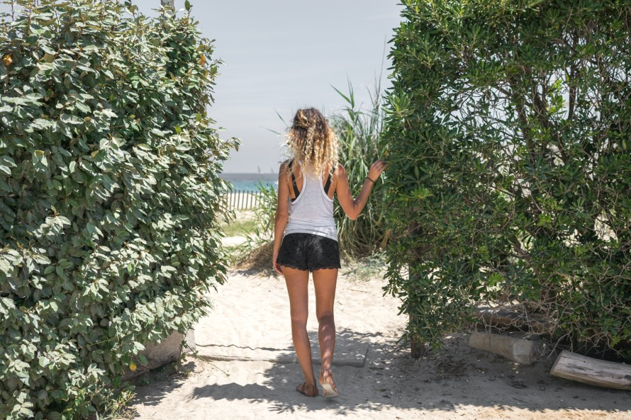 girl standing between two bushes at the beach