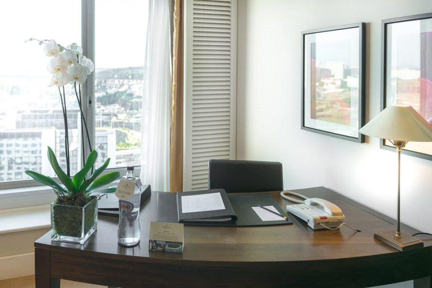 work desk in hotel room with water and flowers