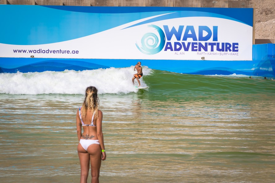 surfer in wave pool girl in bikini watching