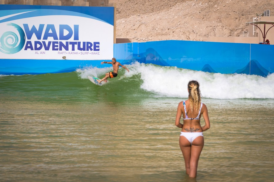 Surfer in wave pool in the desert in Dubai girl in bikini watching