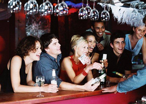 persone appoggiate al bancone di un bar